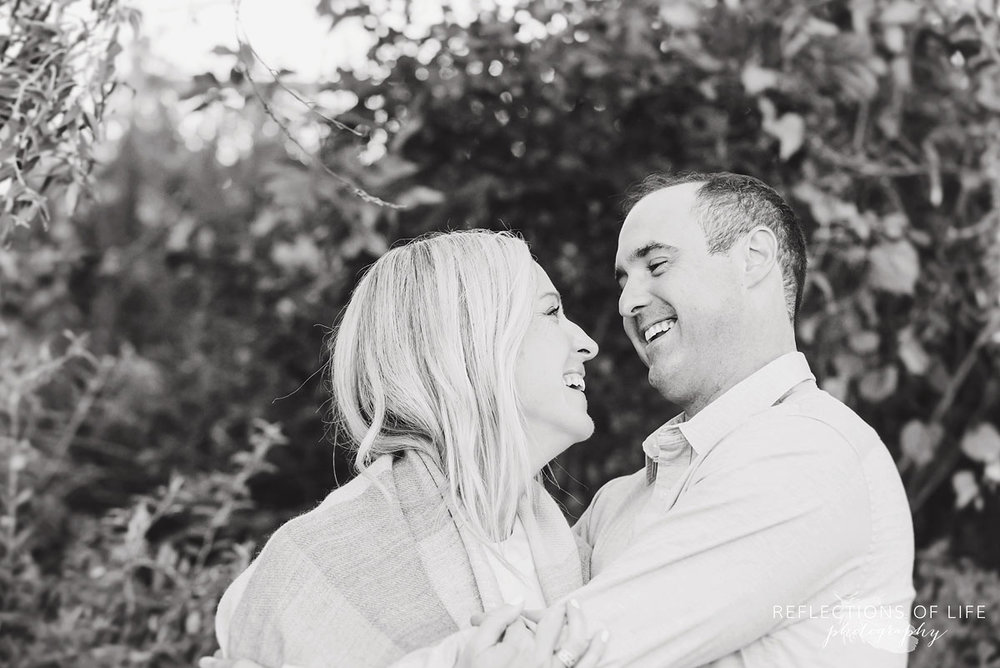 black and white of husband and wife laughing