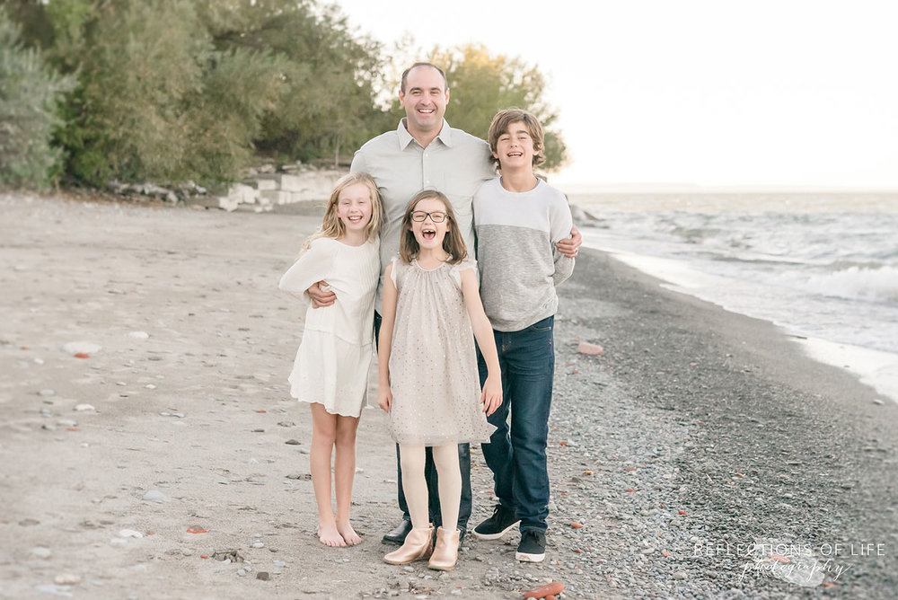 father and children on beach in Niagara Region