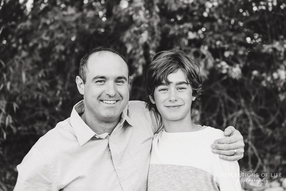 black and white of father with arm around son