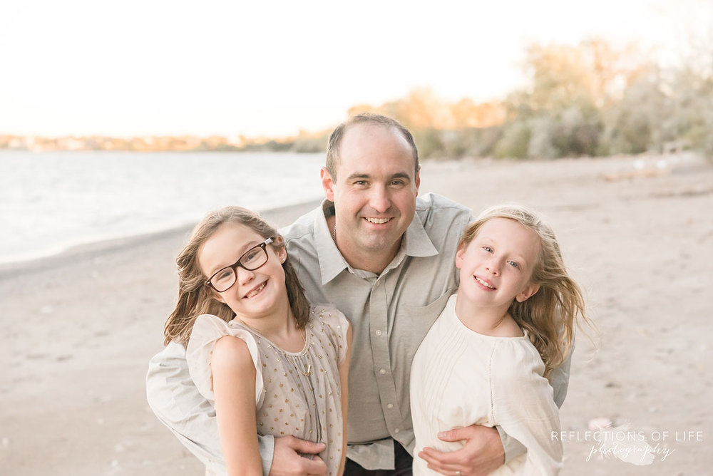 father hugging two daughters