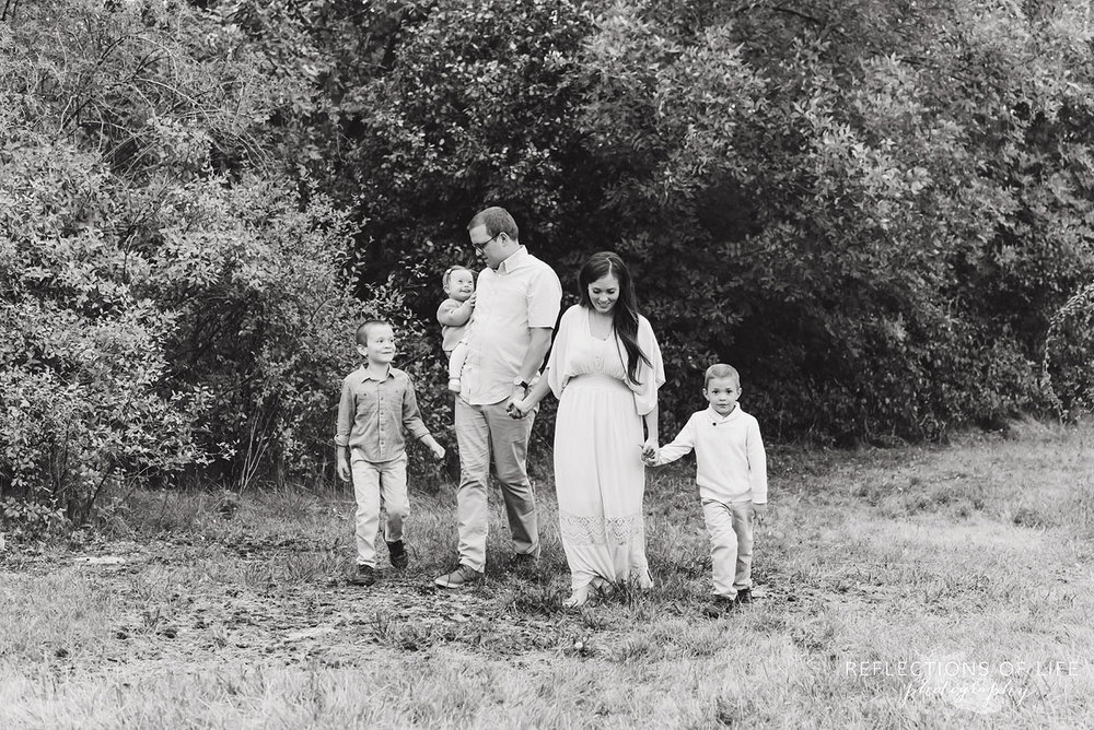 007 family walking in field black and white