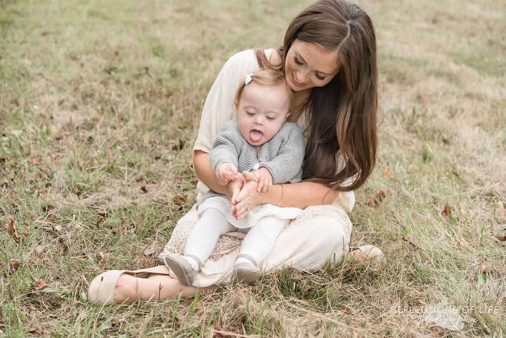030 baby sitting on mamas lap in field