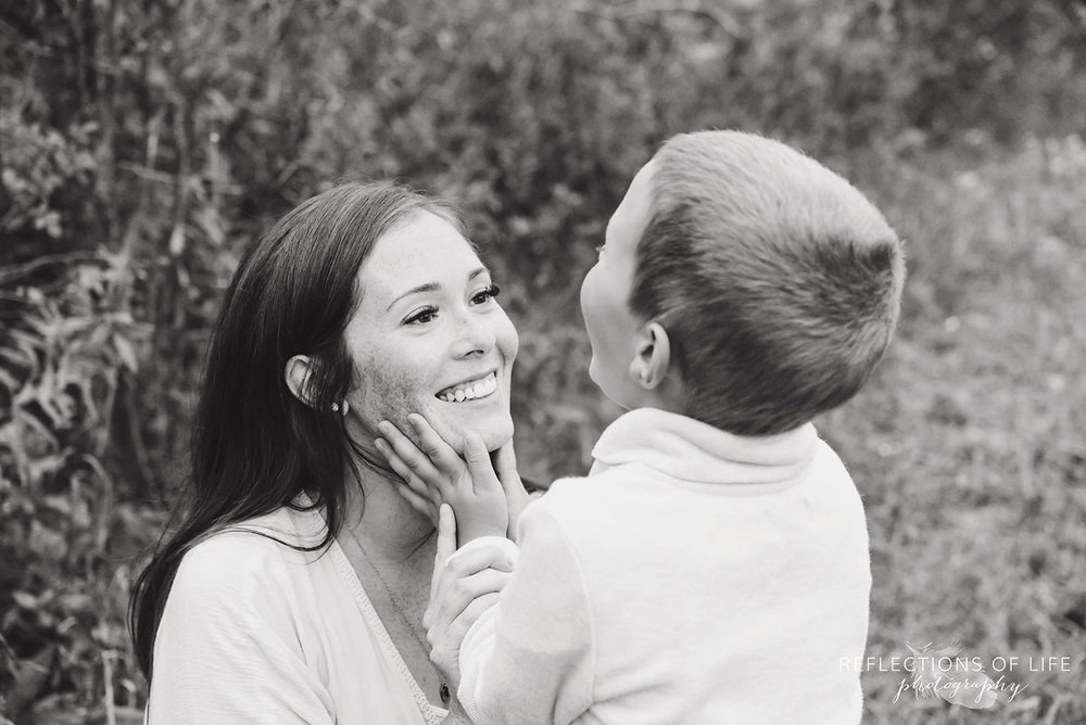 033 son holding mamas face black and white