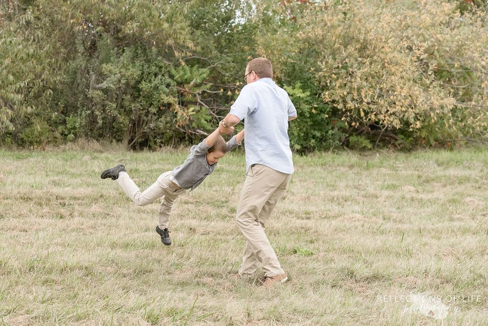 032 father swinging son in field