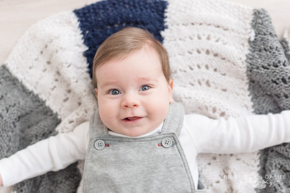 baby smiling on blanket