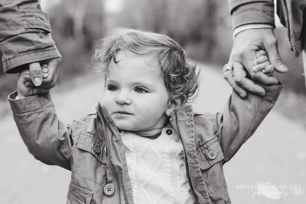 child holding mom and dads hands