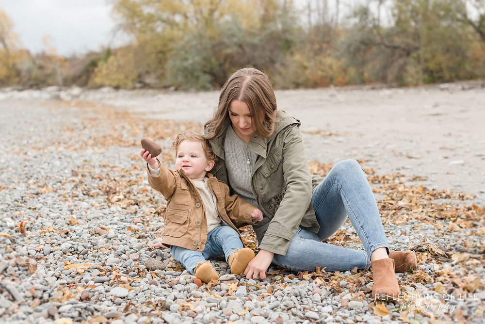 mother and child looking at rocks on the beach