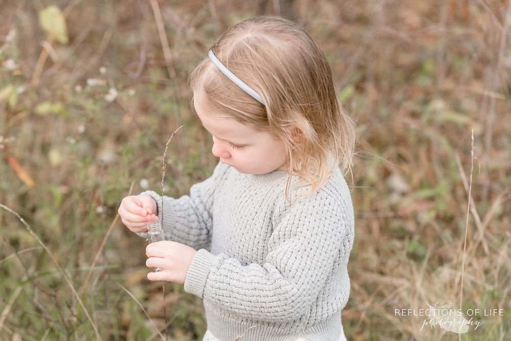 little girl looking at flowers in niagara region