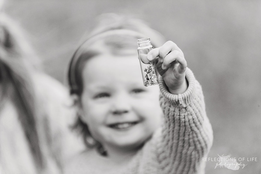 little girl with jar of flowers black and white