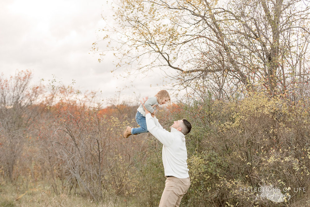 father holding his daughter up in the air
