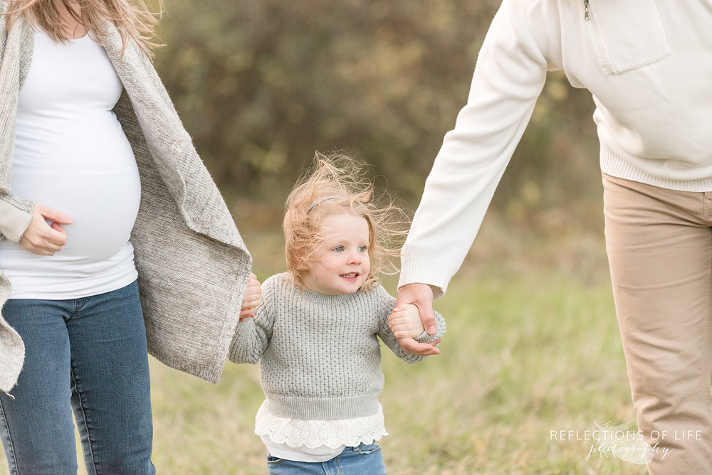 little girl holding her parents hand in cold fall weather