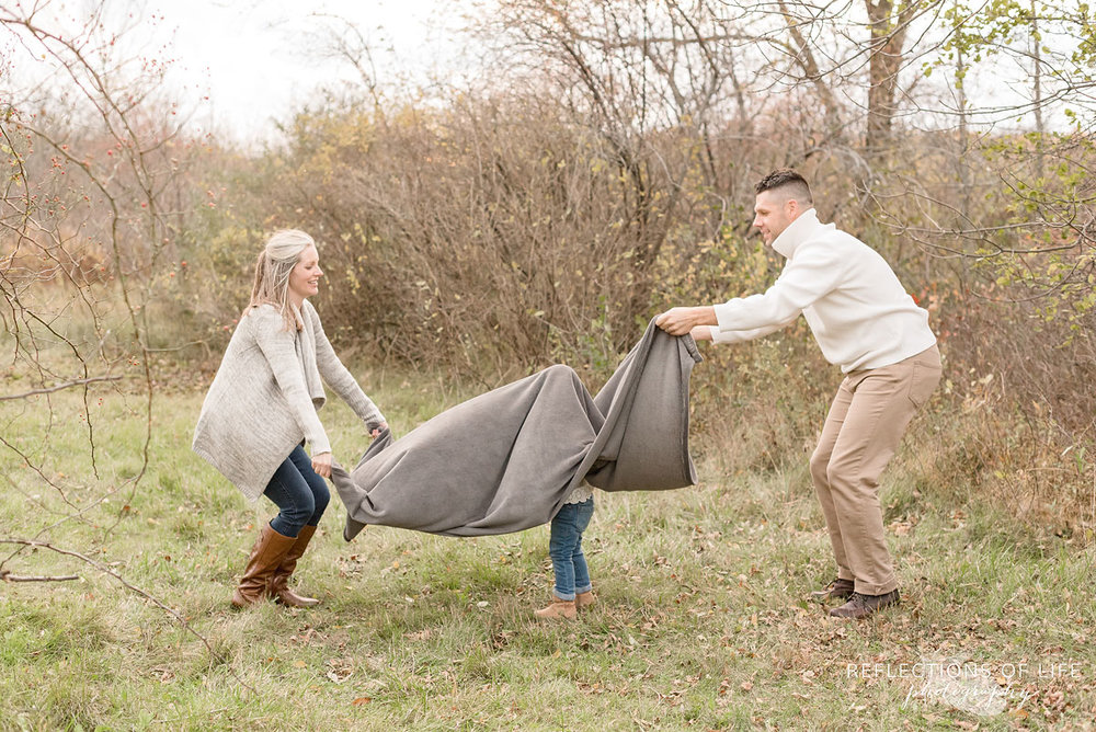 parents waving blanket over daughter