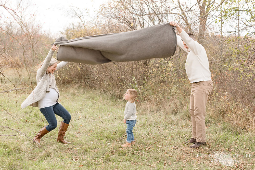 parents holding blanket over little daughter
