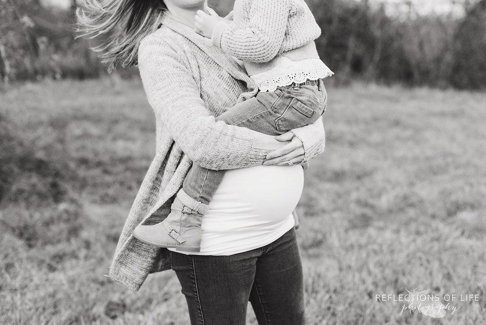mama holding daugheter over belly