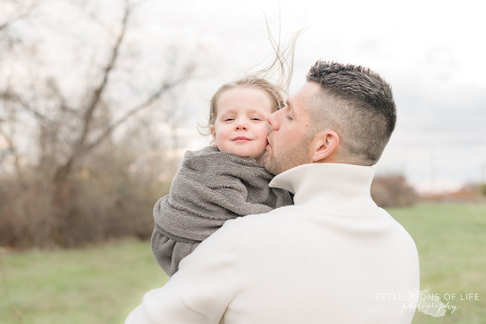 father kissing daughter on the cheek