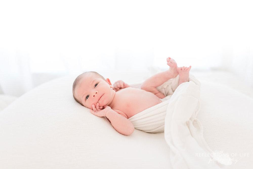 newborn on white blankets