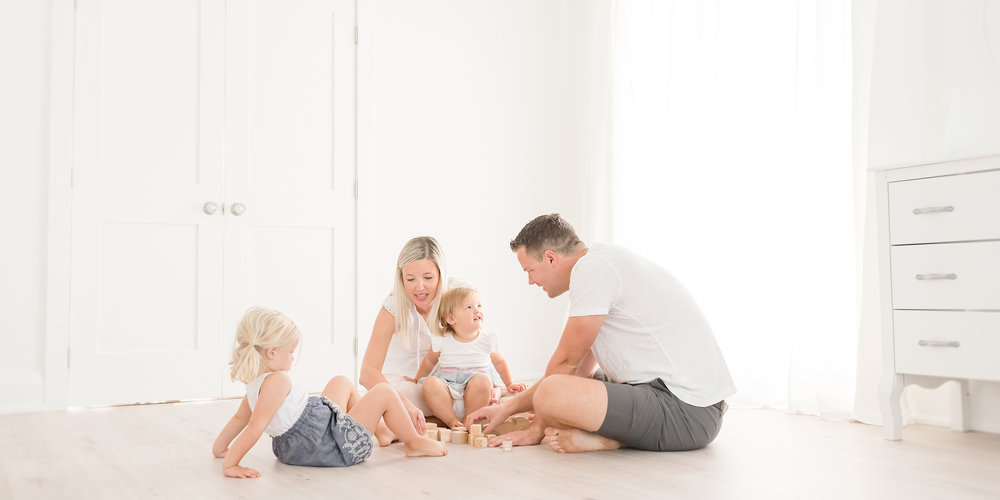 Family playing with blocks in white studio