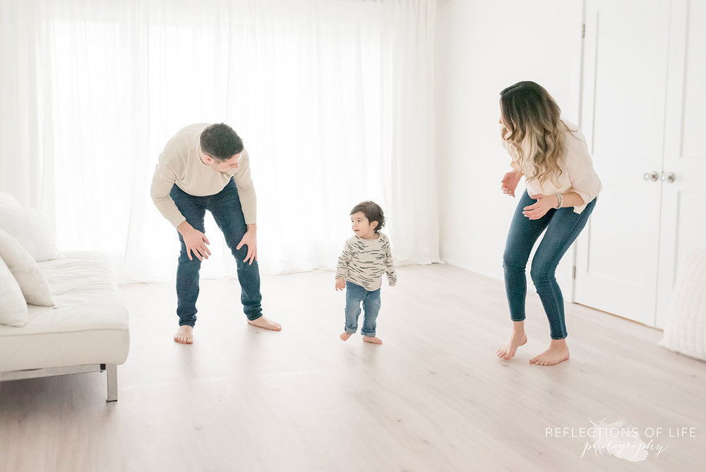 family dancing around in white studio