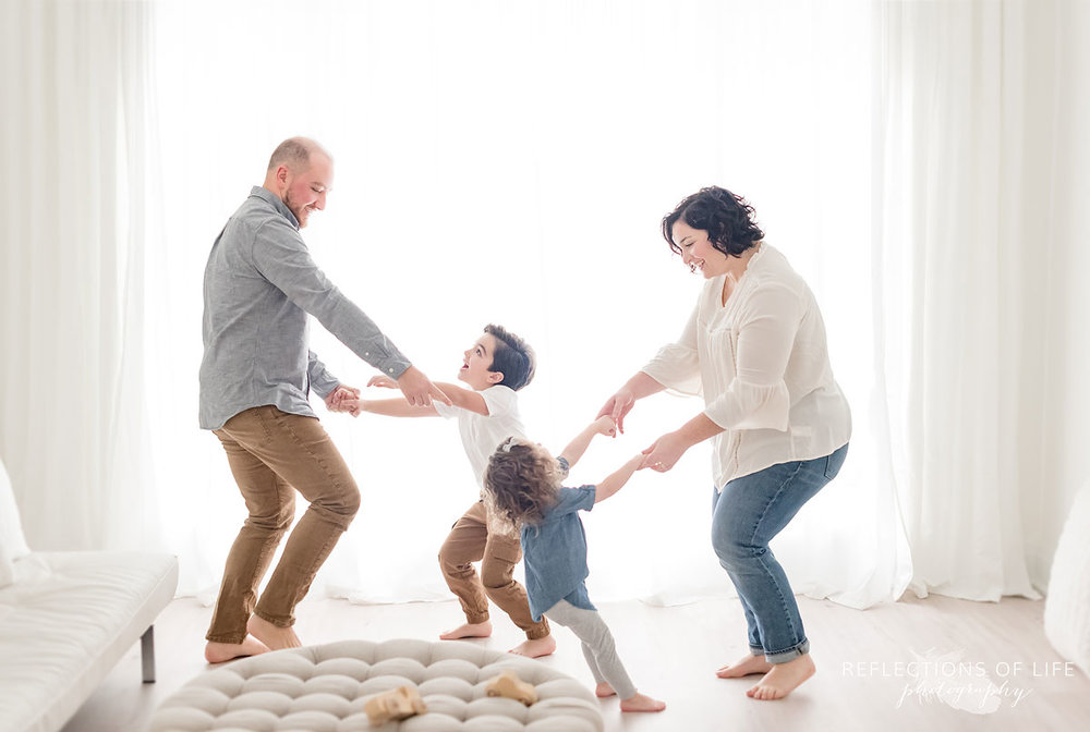 Family dancing in white studio