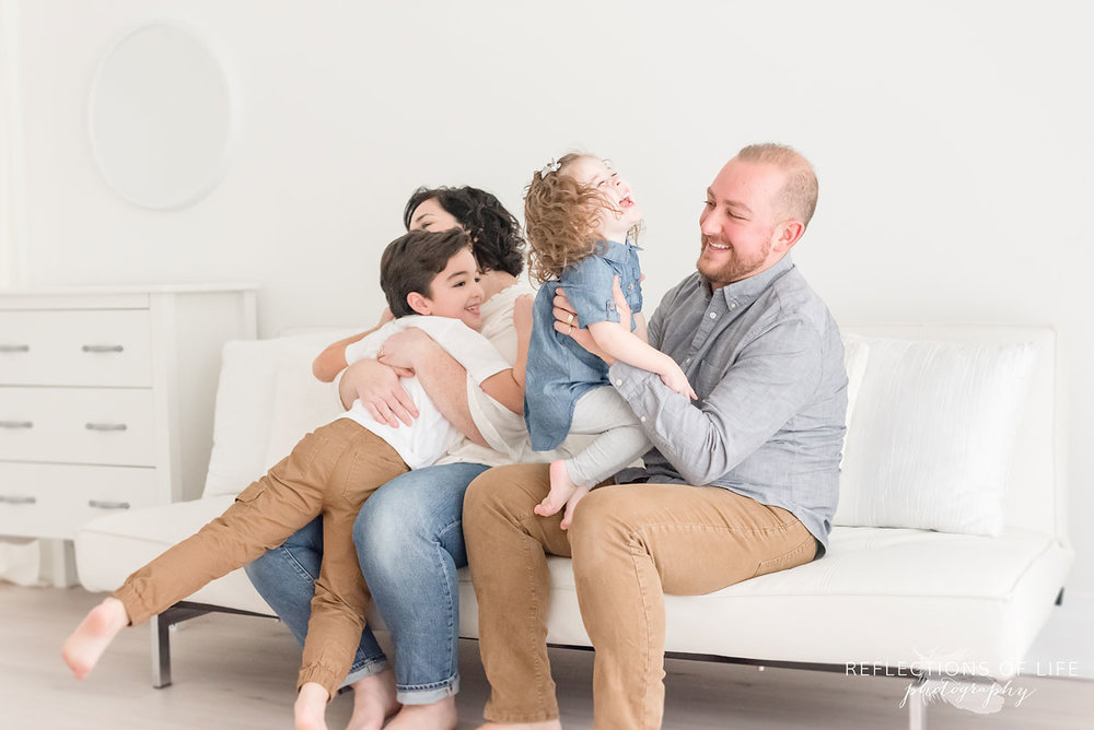 family playing on white couch in grimsby studio