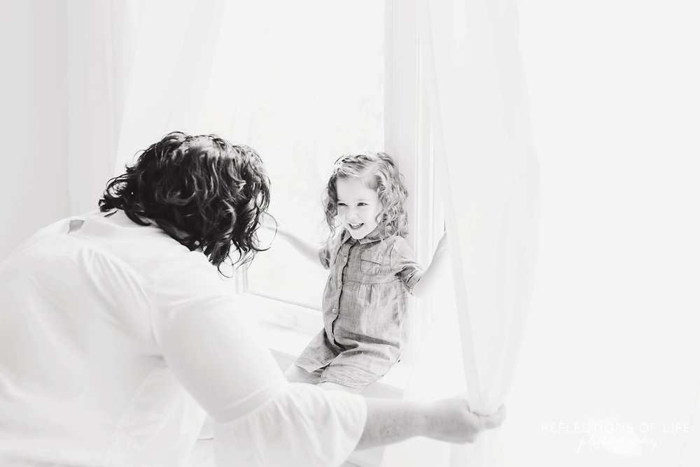 mom opening curtains to daughter black and white