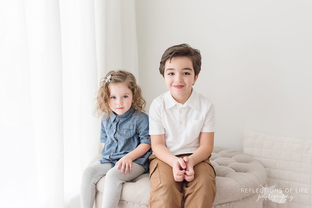 siblings in white studio