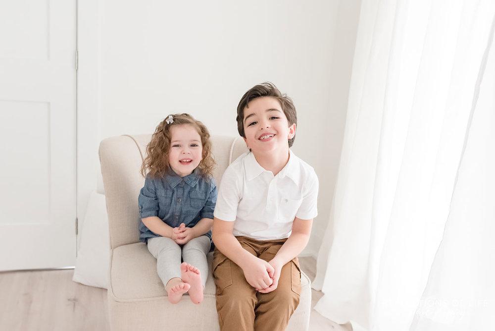 siblings on tan chair