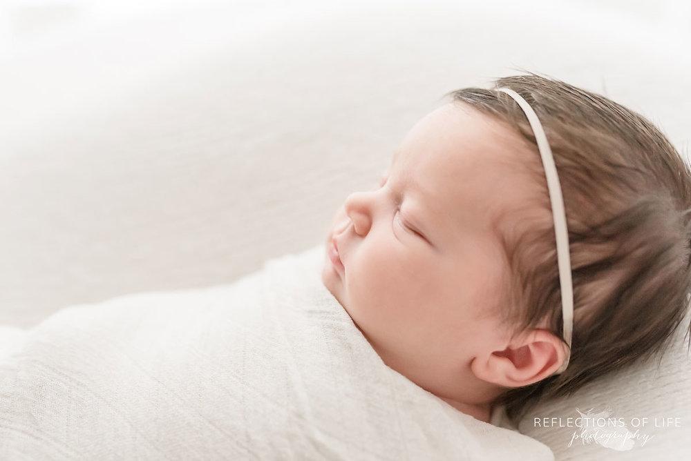 Niagara newborn photographer baby girl with white headband.jpg