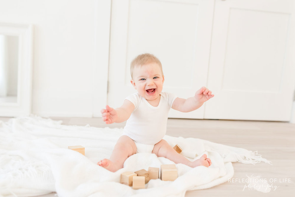 Copy of Copy of Baby boy laughing at the camera and playing with wood blocks