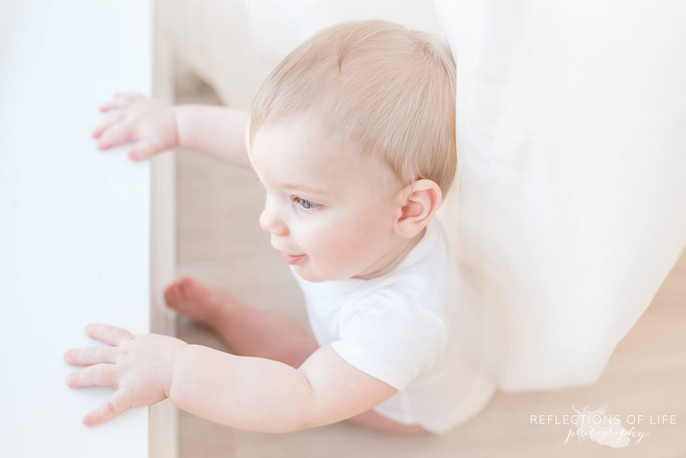 Copy of Copy of Baby boy looking out at the world through a white window