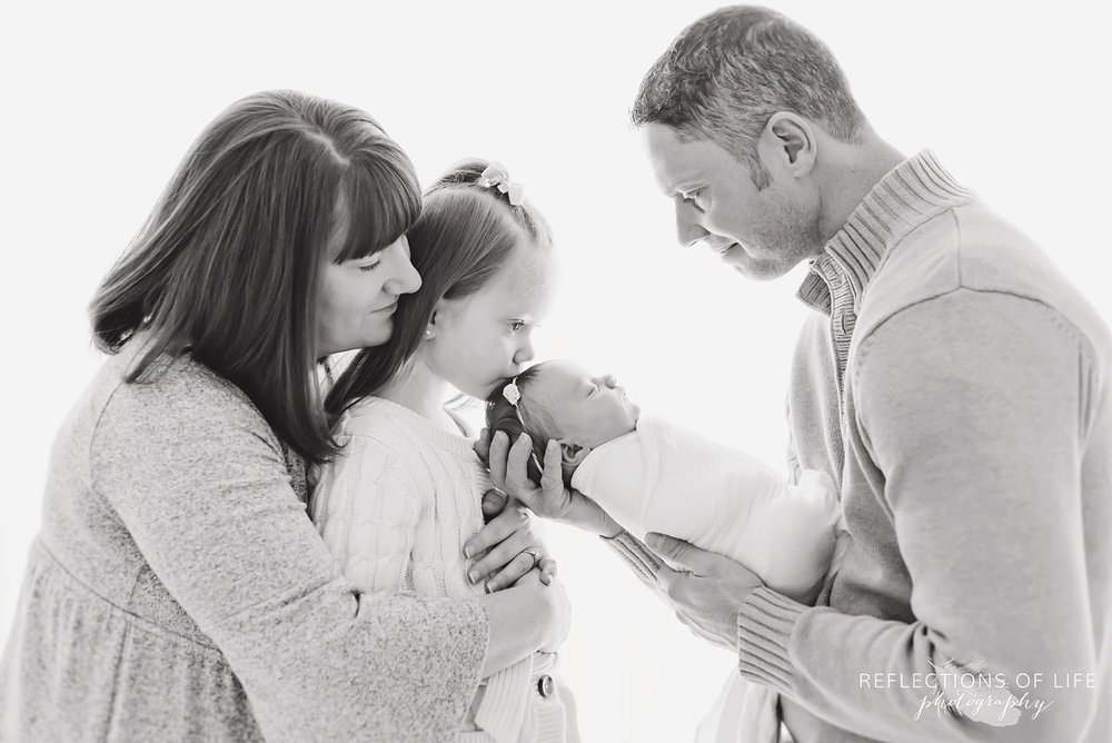 Family of four observes baby while daughter kisses their head black and white.jpg