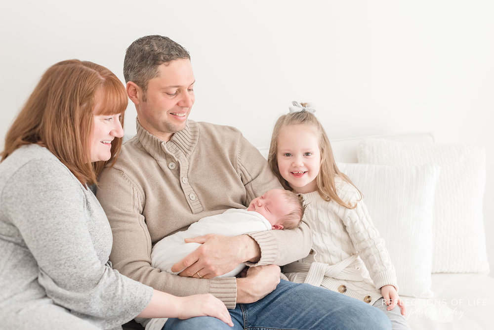 Family of four looks at newborn