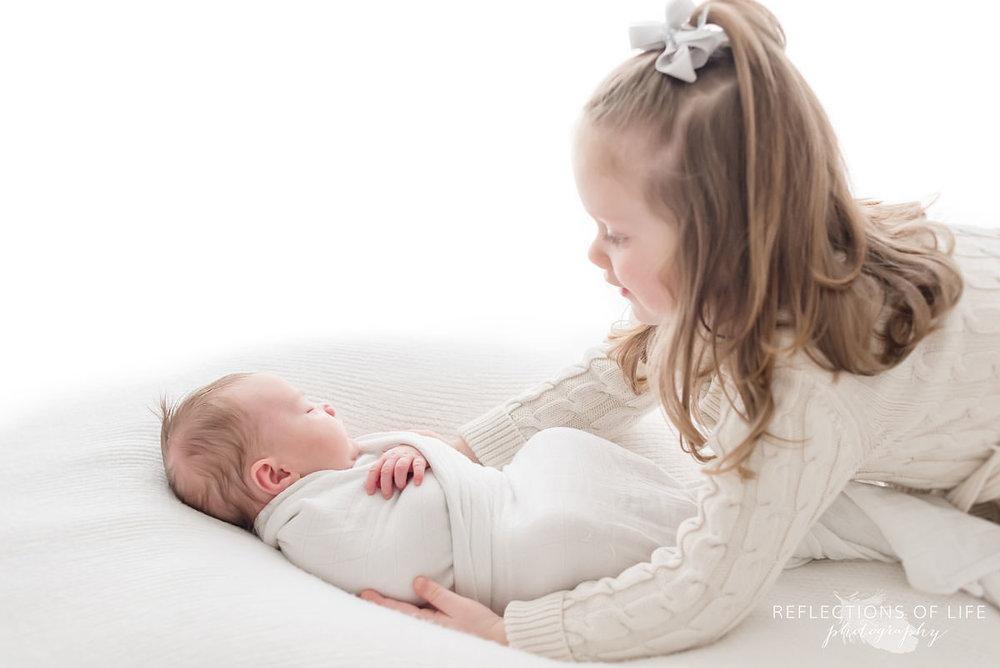 two siblings sister holds baby