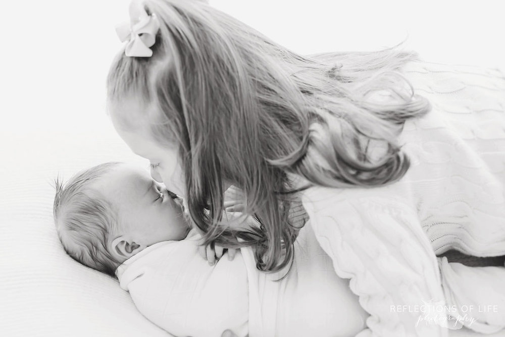 two siblings sister leans over to kiss baby