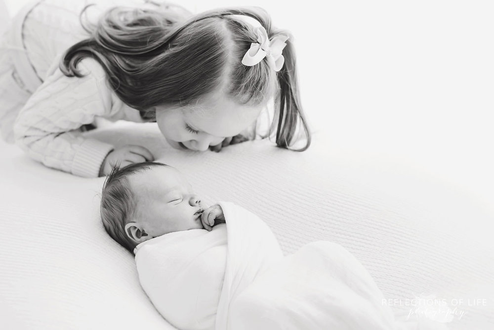 two siblings sister watches over baby sleeping black and white