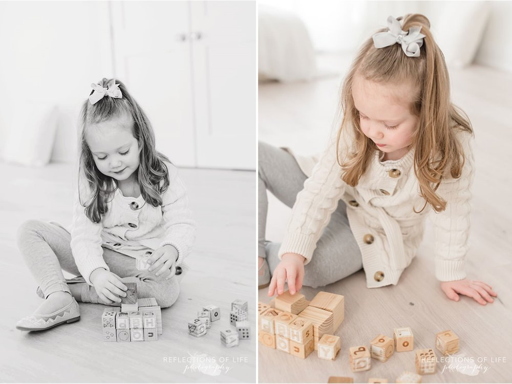 Cute little girl playing with blocks in a natural light studio