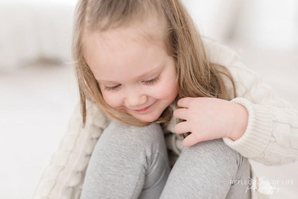 Little girl smiles looking down in Ontario