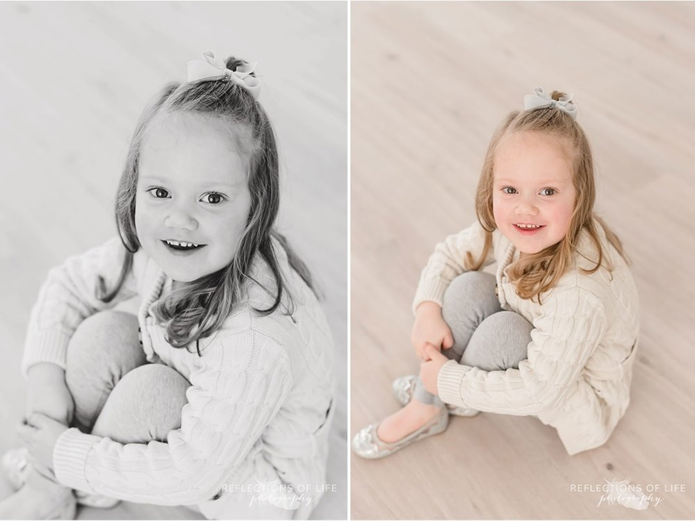 Cute little girl smiles at the camera black and white
