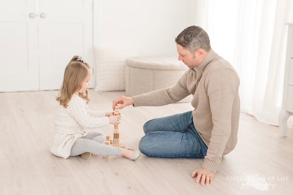 Father and daughter play with blocks in Ontario