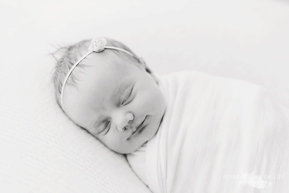 Adorable baby smiles while sleeping in black and white
