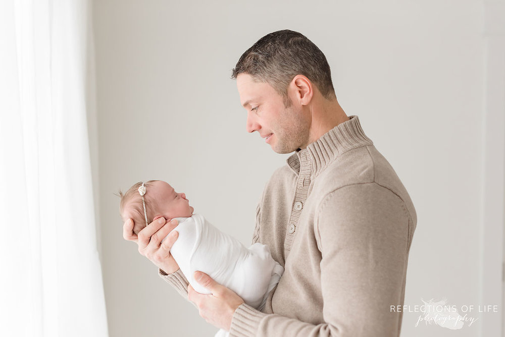 Father looks at sleeping baby profile in natural light studio