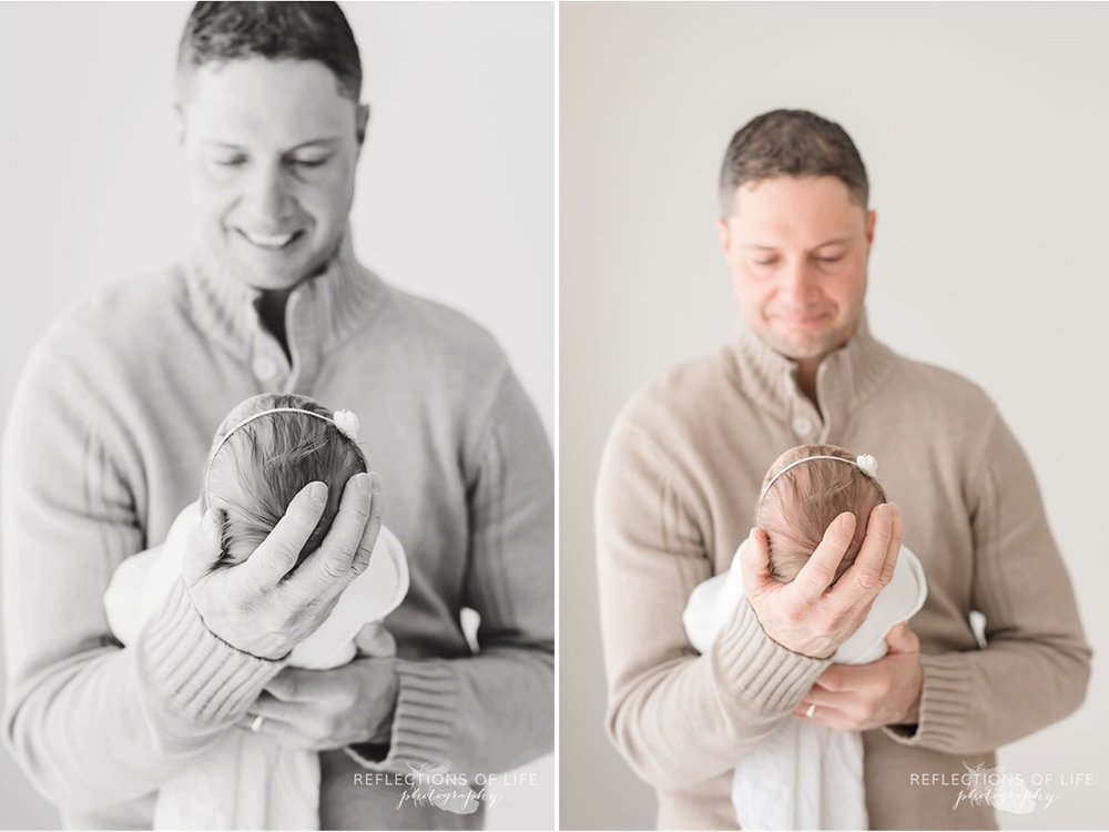 father holds child's head in hand in black and white