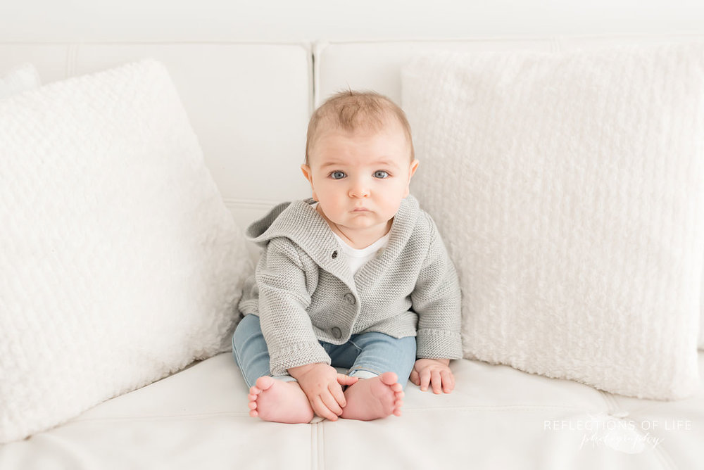baby sits on couch looking at the camera in grimsby