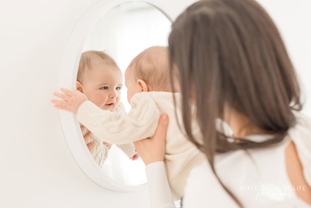baby looks at himself in mirror in natural light studio