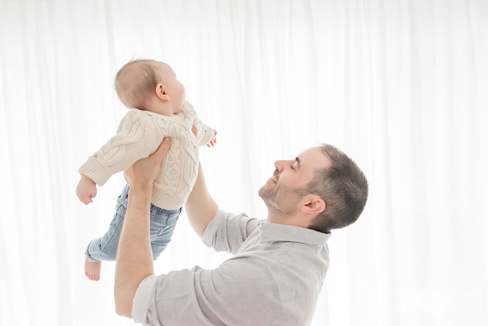 father lifts baby up as baby laughs in natural light studio