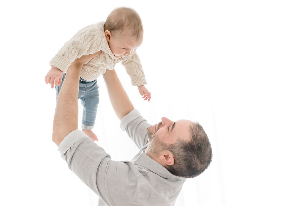 father lifts baby up as he reaches for his face in ontario
