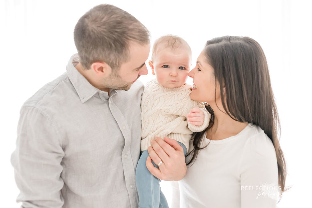 mom and dad admire baby as baby looks at camera in natural light studio
