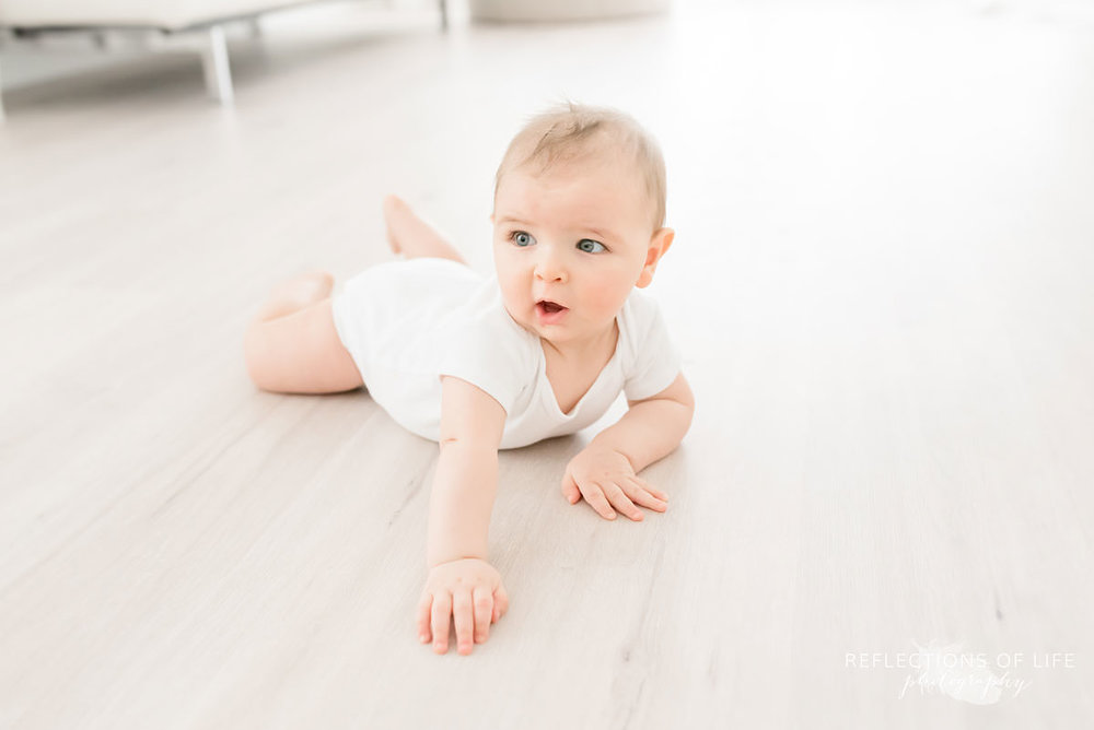 baby lays on ground attempting to crawl in ontario