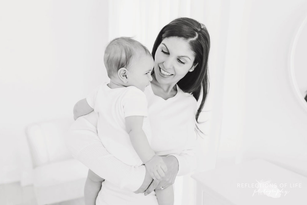 mother smiles at baby in black and white