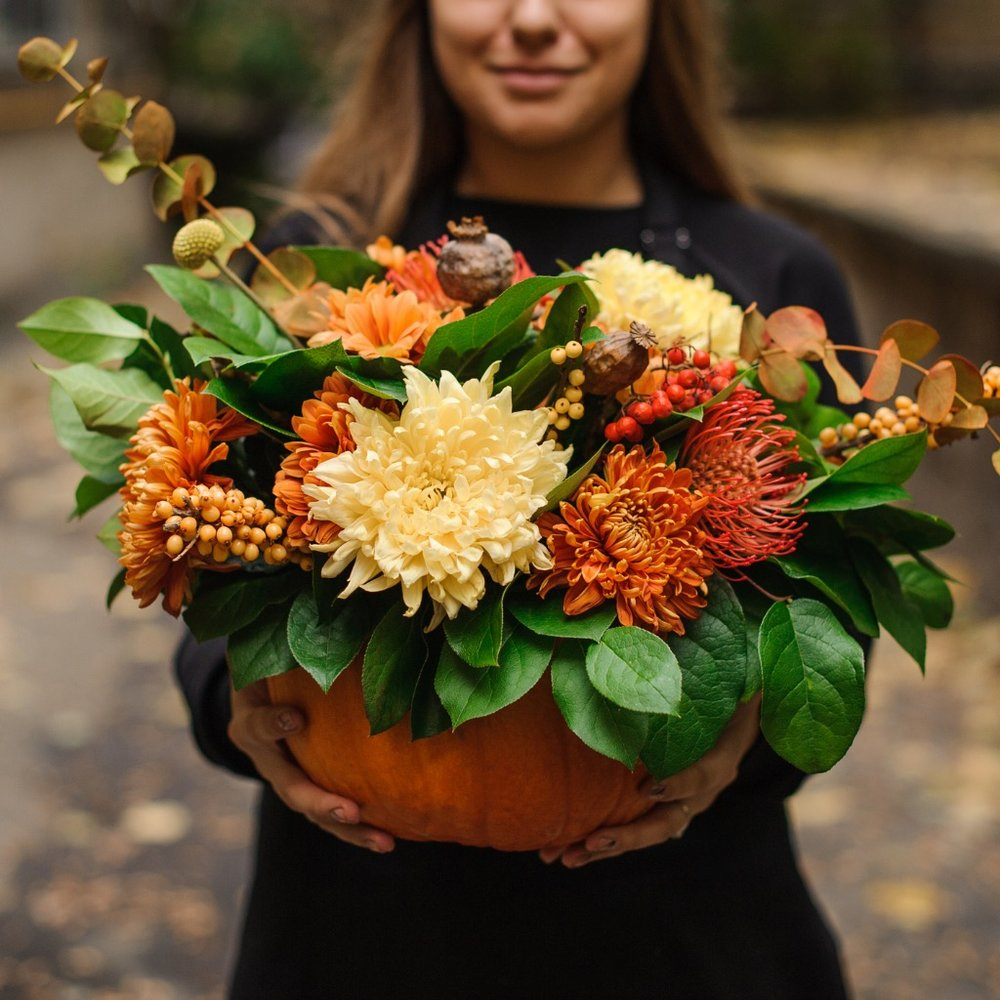 woman-holding-a-pumpkin-with-autumn-flowers-picture-id1008908718.jpg